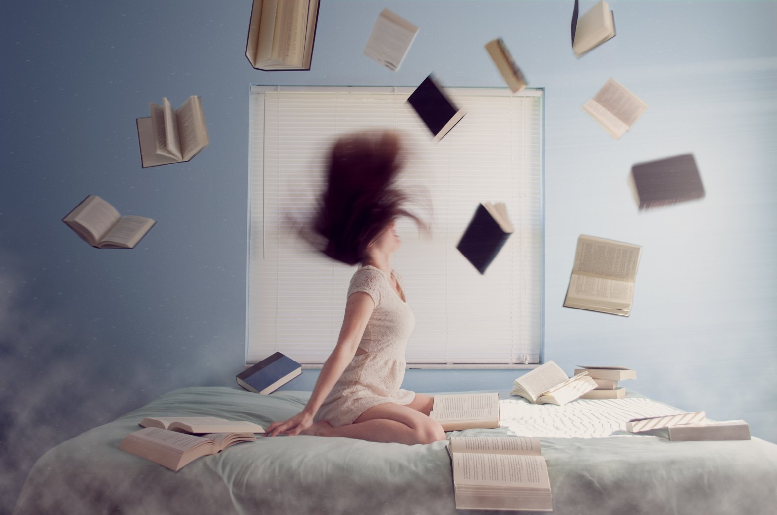 A woman on her bed angrily swinging her head while books float around her Photo by Lacie Slezak on Unsplash