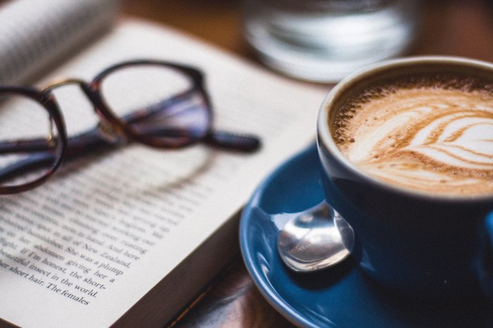 A Photo of a capuccino with a leaf foam design beside an open book with a pair of glasses on top of if by Harry Brewer on Unsplash