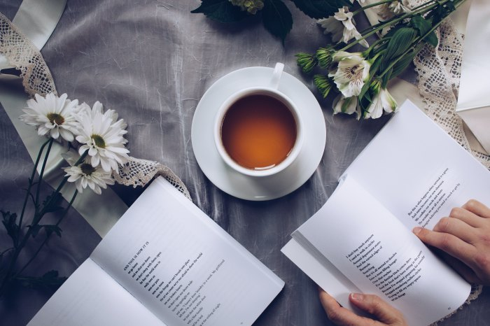 Featured photo of someone reading a book with a cup of tea and another book sitting aside, the table is filled with white flowers Photo by Thought Catalog on Unsplash