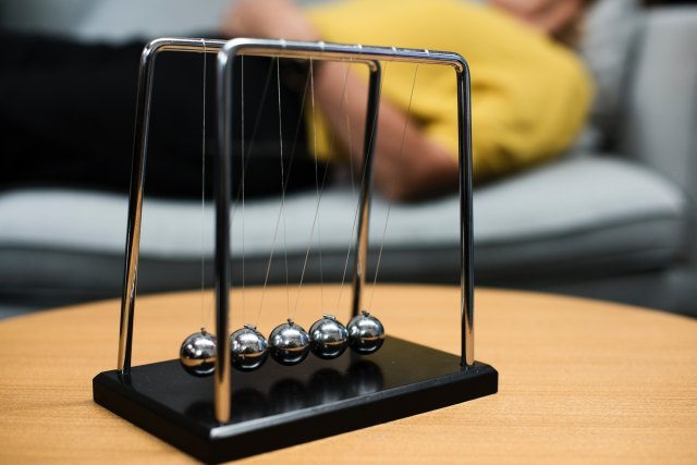 selective focus photography of gray Newton's Cradle on brown wooden table Photo by rawpixel on Unsplash