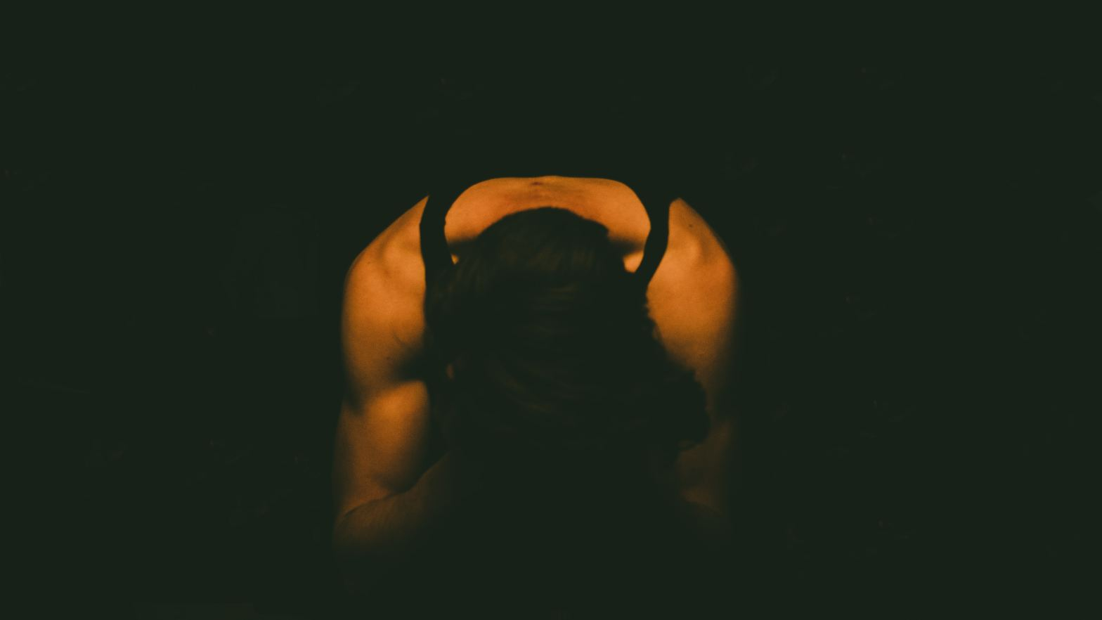 A woman crouching on the ground in the dark